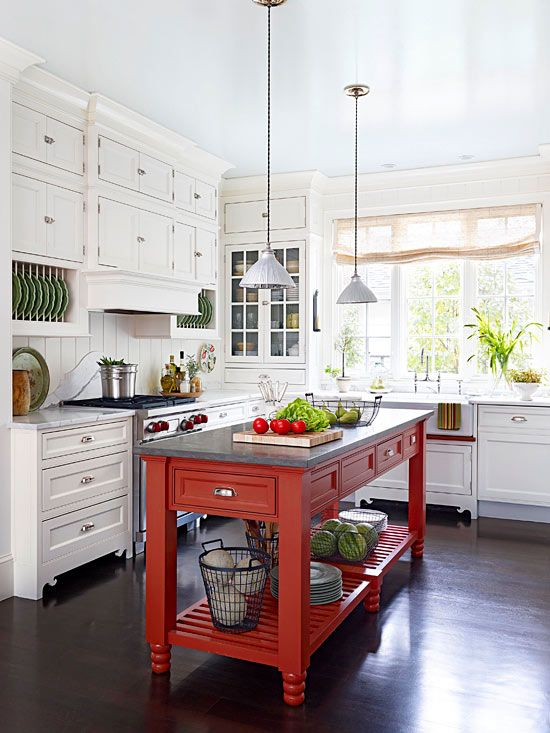 A contrasting red narrow kitchen island with a granite countertop