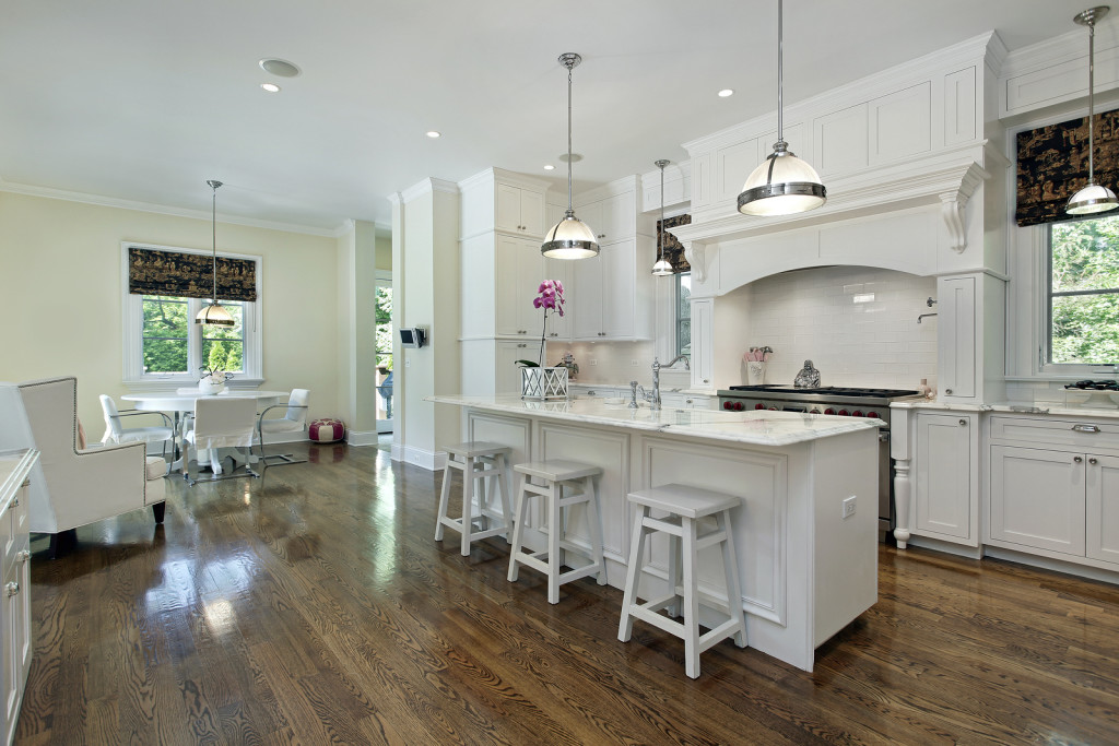 Large kitchen in luxury home with white cabinetry and narrow island with seating